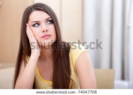 Portrait of a young worried beautiful woman looking up - stock photo
