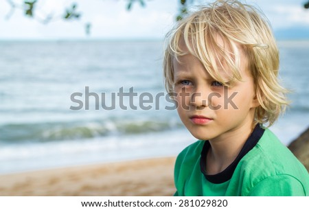 Portrait of a young worried boy deep in thought at the beach - stock photo