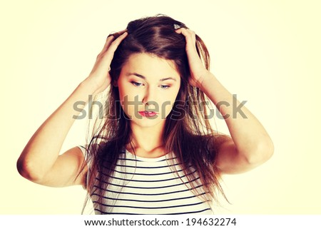 Portrait of a young worried caucasian female teen holding her hands next to her head - stock photo