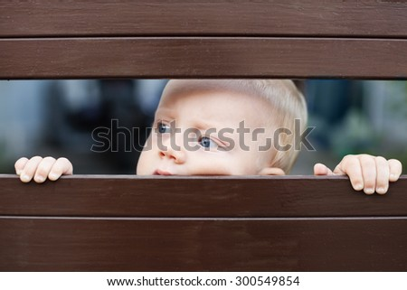Portrait of abandoned little baby boy with staring blue eyes, sad and lonely face expression, looking out through fence and waiting for parents. Family relationships, children feelings and emotions - stock photo