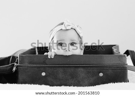Portrait of aborable baby lying in vintage bag - stock photo
