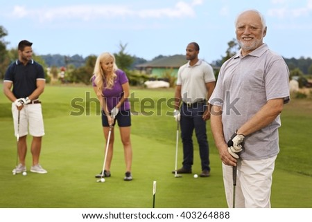 Portrait of active happy senior on the golf course, people playing at the background. - stock photo
