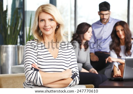 Portrait of active senior business woman sitting at meeting while business people working background. - stock photo