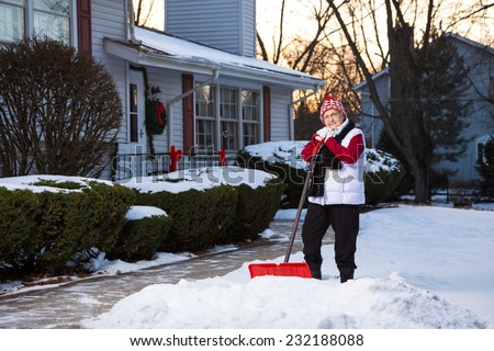 Portrait of Active Senior Citizen with Snow Shovel in Front of Home - stock photo