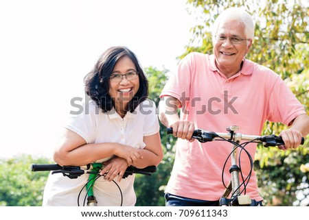 Portrait of active senior couple smiling while standing on bicycles outdoors in summer