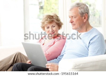 Portrait of active senior couple surfing on internet. - stock photo