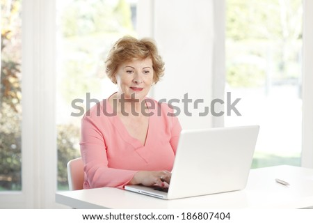 Portrait of active senior woman sitting at desk and working on laptop.  - stock photo