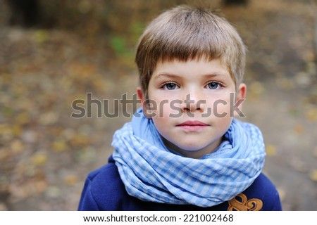 Portrait of adorable and fashionable little boy with big blue eyes in blue coat and scarf outdoor at the nice autumn day - stock photo