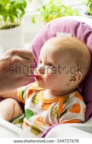 Portrait of adorable baby boy eating his first solid food - stock photo
