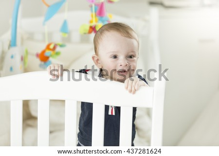 Portrait of adorable baby boy standing in bed and leaning on fence - stock photo