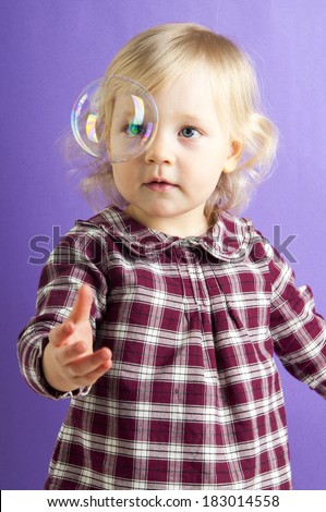 Portrait of adorable baby girl in checkered shirt having fun with soap bubble isolated on purple background - stock photo