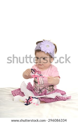 Portrait of adorable baby girl on blanket in pink clothes on a white background