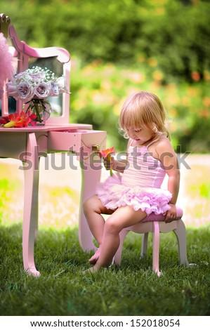Portrait of adorable baby girl wearing ballet costume in beautiful garden background - stock photo