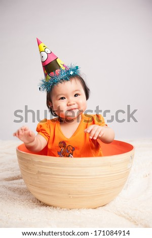 Portrait of adorable baby sitting in basket - stock photo