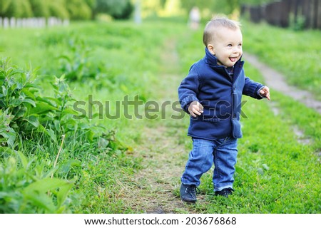 Portrait of adorable blond baby boy with blue eyes in the blue coat  - stock photo
