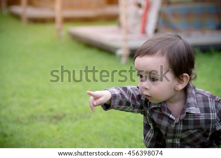 portrait of adorable blond baby toddler sitting in green grass  - stock photo