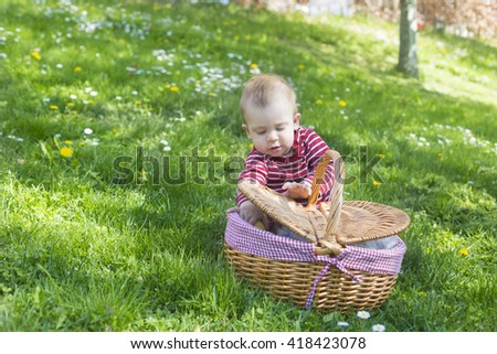 portrait of adorable blond baby toddler sitting in green grass with picnic basket in park, playing and curious into basket - stock photo