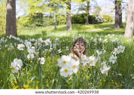 portrait of adorable blond young girl in preschool age sitting in the middle of forest meadow with many narcissus white flowers - stock photo