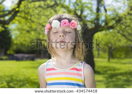 portrait of adorable blond young girl in preschool age standing with closed eyes and enjoying sun, wearing wreath with  flowers on head on green lawn in park - stock photo