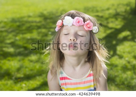 portrait of adorable blond young girl in preschool age wearing flowers in hair and making air kiss outdoors - stock photo