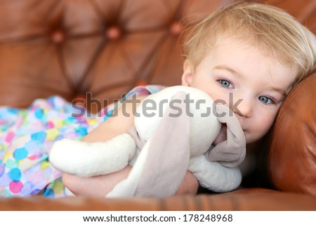 Portrait of adorable blonde toddler girl lying on leather sofa holding rabbit toy in her arms - stock photo