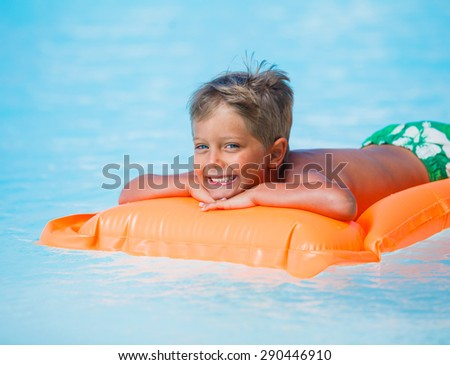 Portrait of Adorable boy relaxing at swimming pool - stock photo