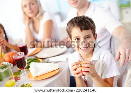 Portrait of adorable boy with apple looking at camera with his family on background - stock photo