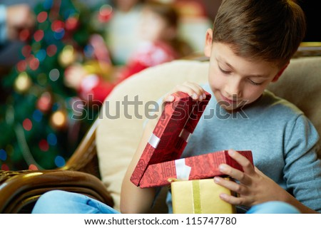Portrait of adorable boy with giftboxes looking into one of them - stock photo