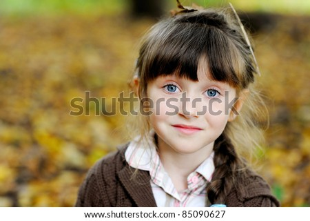 Portrait of adorable child girl with blue eyes in autumn forest