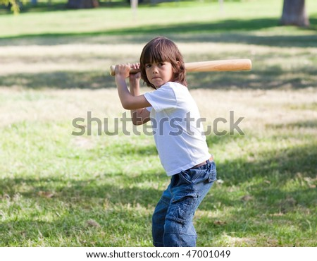Portrait of adorable child playing baseball in the park - stock photo