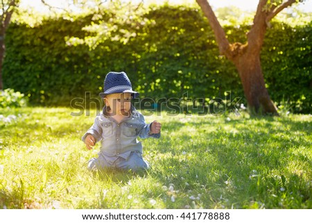 portrait of adorable cute baby toddler wearing denim shirt and blue hat sitting in fresh green grass in park or forest in sunlight  - stock photo