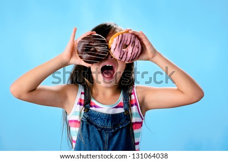 Portrait of adorable cute girl kid with donut - stock photo