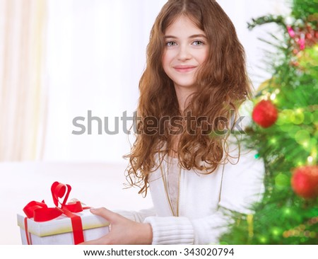 Portrait of adorable girl celebrating New Year at home near Christmas tree, receiving gift box, enjoying festive surprise - stock photo
