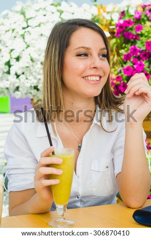 Portrait of adorable girl smiling while drinking smoothie at the mall outside