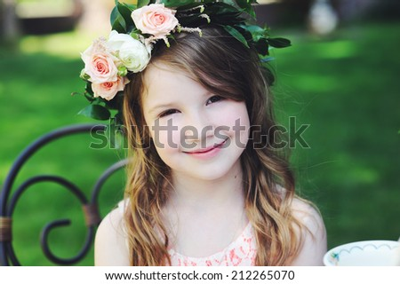 Portrait of adorable kid girl with flower wreath outdoor in the garden  - stock photo