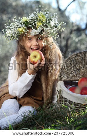 Portrait of adorable kid girl with flower wreath outdoor in the garden. Beautiful girl with curly long hair eating an apple. A child and a basket of apples. - stock photo