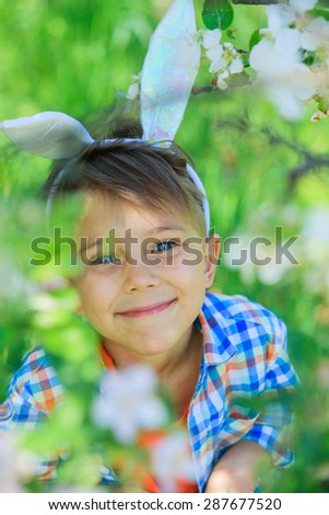 Portrait of adorable little boy wearing bunny ears playing in blossoming apple garden on spring day - stock photo