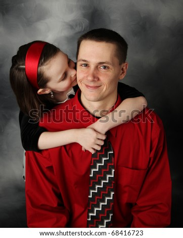 Portrait of adorable little girl and handsome father in dressy clothing hugging and kissing on cheek - stock photo