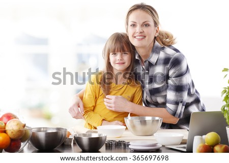 Portrait of adorable little girl baking cookies with her mother in the kitchen.