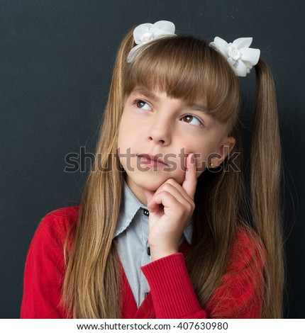Portrait of adorable little girl dreaming about something at the black chalkboard in classroom - stock photo