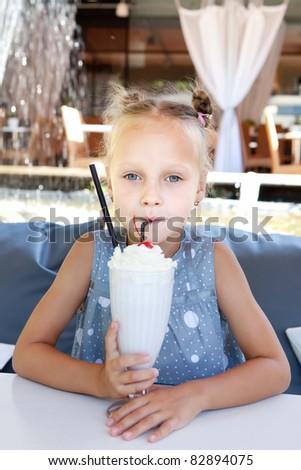 Portrait of adorable little girl drinking fresh milkshake at the cafe outdoors - stock photo