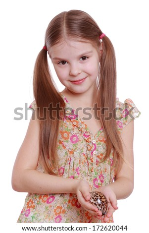 Portrait of adorable little girl holding sea shell