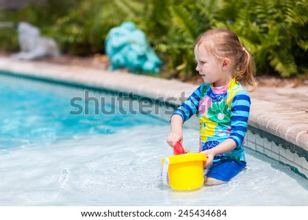 Portrait of adorable little girl in a swimming pool with toys - stock photo