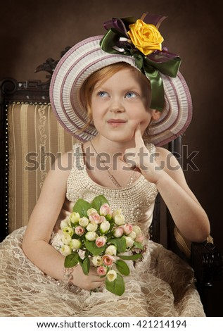 Portrait of adorable little girl in hat and with flowers sitting on chair in studio