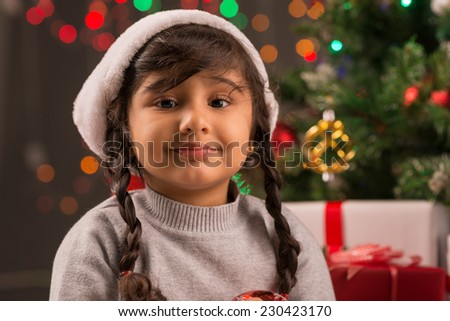 Portrait of adorable little girl in Santa Claus hat - stock photo