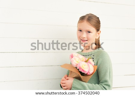 Portrait of adorable little girl of 8-9 years old, wearing warm green pullover, holding spring pink flowers, standing against white wooden background, mother's day concept - stock photo