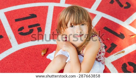 Portrait of adorable little girl on playground - stock photo