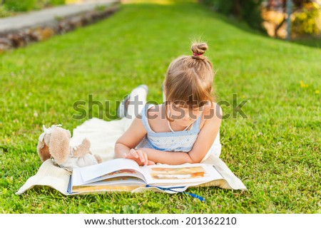 Portrait of adorable little girl resting outdoors and reading a book on a nice summer evening - stock photo