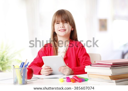 Portrait of adorable little girl using digital tablet while sitting at desk at home.