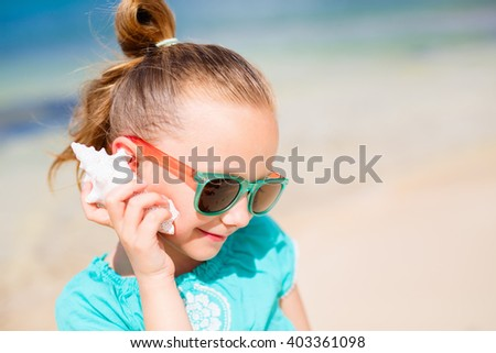 Portrait of adorable little girl with a seashell - stock photo